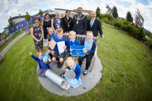 DWH donate da time-capsule to Chapelford Village Primary School to be opened in 100 years. Pictured front Sophie Travis aged 9 with the student ambassadors  Ms Adams Ms Earps (core) and Ms Hewson Mayor of Warrington Cllr Faisal Rashid and his Mayoress wife Aleeza and Andrew Taylor, Planning Director DWH