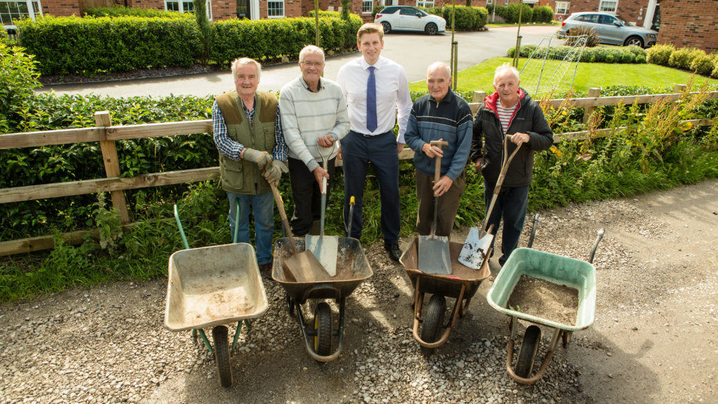 Volunteers from the allotment site stand on the repaired road with David Wilson Homes' James Griffiths