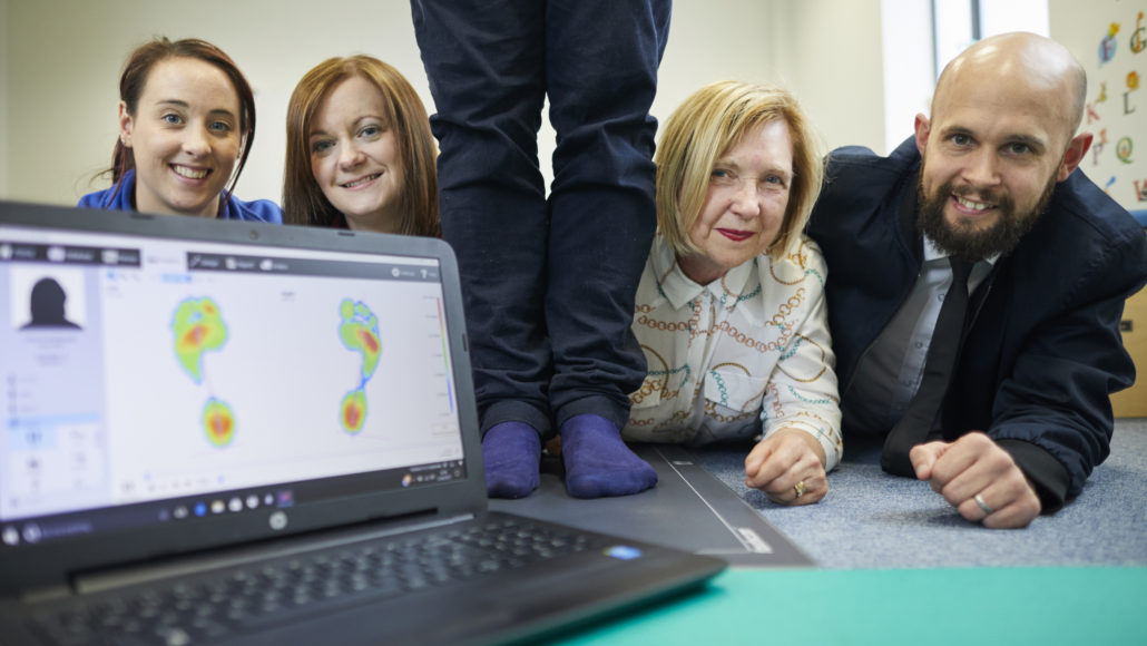 DWH David Wilson Homes donate a foot pressure measuring pad to charity Brainwave in Warrington.  Pictured L-R Therapist Carol Galashan, and from DWH Cheryl Rothwell, feet, Pauline Mcginty and Mark Lucy.